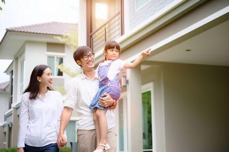 famille marchant sur la nouvelle maison modèle à la recherche d'un avenir vivant, nouvelle famille rencontre une nouvelle maison Banque d'images