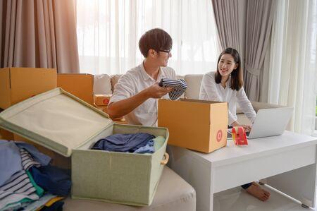 amante de la pareja que vende ropa de segunda mano o vestidos usados en línea, lista para empaquetar, verifique la dirección de entrega al pedido de destino