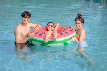 Family enjoy and happy in swimming pool in summertime, feel comfort and relax together