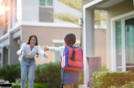 girl daughter running exciting to mother welcome home after school study Imagens