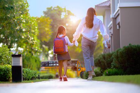 mère sur le chemin envoyant sa fille au bus scolaire le premier jour d'apprentissage