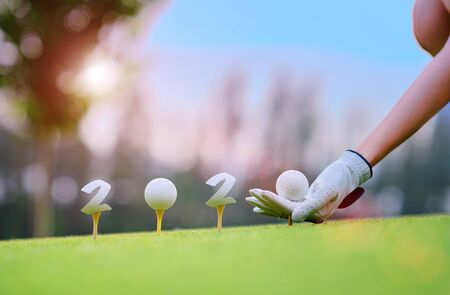 Hand of woman golfer laying golf ball onto wooden tee on tee off in the golf course with welcoming year 2020 celebration and greeting season through the year Фото со стока