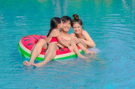 Family enjoy and happy in swimming pool in summertime, feel comfort and relax together Фото со стока