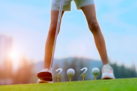 golf balls symbol laying golf ball onto wooden tee on tee off in the golf course with welcoming year 2020 celebration and greeting season through the year Фото со стока