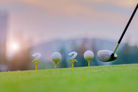 golfball laying onto wooden tee on tee off in the golf course with welcoming year 2020 celebration and greeting season through the year Stock Photo