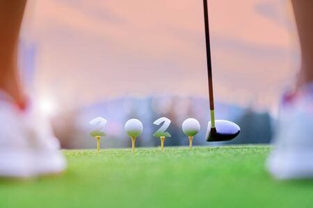 golfball laying onto wooden tee on tee off in the golf course with welcoming year 2020 celebration and greeting season through the year Фото со стока