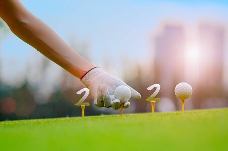 Hand of woman golfer laying golf ball onto wooden tee on tee off in the golf course with welcoming year 2020 celebration and greeting season through the year Stock Photo