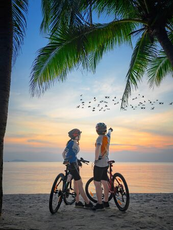 couple lover riding bicycle along the sea beach under coconut trees at sunset, relaxation at the end of the day