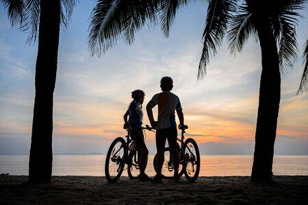 Silouhette eines Paarliebhabers, der bei Sonnenuntergang unter Kokospalmen Fahrrad am Meeresstrand entlang fährt, Entspannung am Ende des Tages?