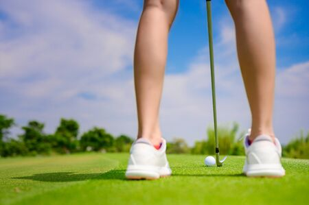 Pitching wedge going to taking golf ball away from edge of the green to destination hole on the green, final destination for the winner of the woman golfer