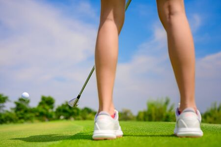 Pitching wedge taking golf ball away from edge of the green to destination hole on the green, final destination for the winner of the woman golfer
