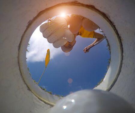 vue du bas angle inférieur du trou de golf, main d'une joueuse de golf en train de retirer une balle de golf du trou sur le green après avoir réussi à remporter un gagnant