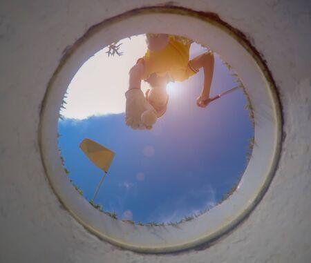 vue du bas angle bas du trou de golf, une balle de golf dans la main d'un joueur de golf étant enlevée du trou sur le green par une joueuse de golf après avoir réussi à gagner