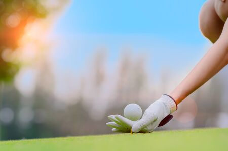 hand of young woman golf player holding golf ball laying on wooden tee pin on T-OFF, prepare and ready to hit the ball to the destination target