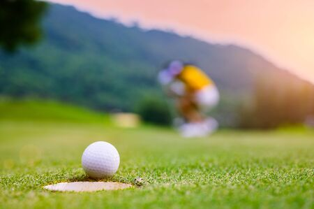 golf ball run through almost success drop to hole on the green with exciting watching by woman golf player in background Banco de Imagens