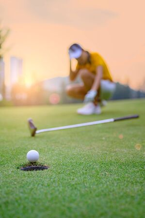golf ball putting unsuccessfully into hole on the green by young woman golf player is acting of an upset or disaster, disturb or disappointed in background