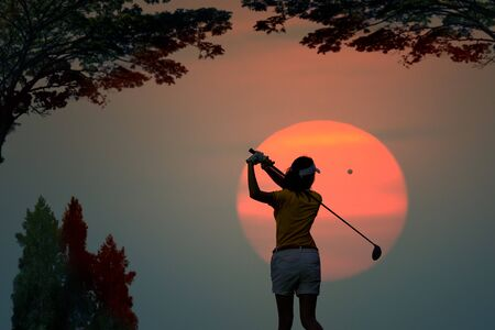 silhouette of woman golf player in action at the end of downswing hit a golf ball to destination in the fairway, best concentrate to destination of life CONCEPT Banco de Imagens