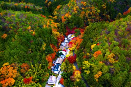 Aerial top view of the Countryside village of Japan present in season change of Autumn, scenery view of Japan village living in between mountain and hills at time of Autumn Archivio Fotografico
