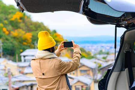 Woman traveller enjoy taking photo the scenery view of autumn village in Japan countryside, Travel all around Japan countryside by car transportation