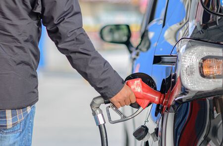 hand of driver takes gas pump nozzle into oil tank, refill fuel gas to oil tank by self services during travel in trip