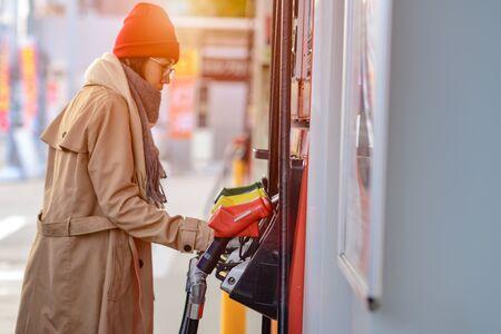 benzinepompmondstuk in benzinestation in stopcontact klaar om te vullen door zelfbediening van vrouwelijke reiziger