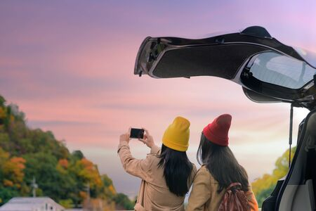 Woman traveller tourist enjoy walks to taking photo the scenery view of autumn village in Japan countryside, Travel all around Japan countryside by car transportation