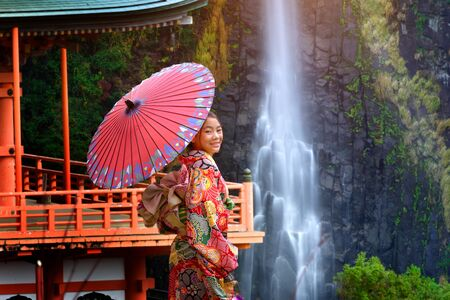 woman in old fashion style wearing traditional or original Japanese dressed,  stand alone in the middle garden park of the shrine, japan old fashion style attractive with waterfall in background