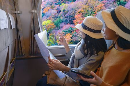Woman traveller tourist enjoy the trip on train transport of the season change autumn at on the way of traveling from town to town countryside