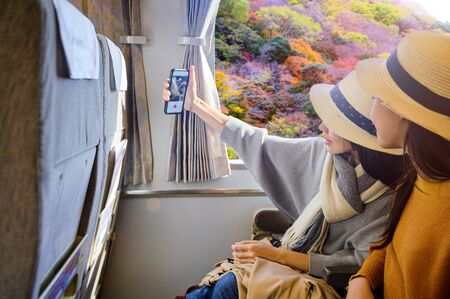 Women traveller tourist enjoy the trip on train transport at on the way of travel from town to town countryside, selfie happy on the train with autumn blooming beside railway, Visit Japan travel