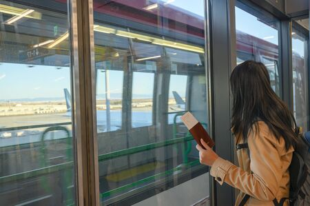 passport and boarding pass in hand of woman passenger awaiting for transit train from terminal to another terminal, airport transit in terminal, transfer in airport terminal by train services