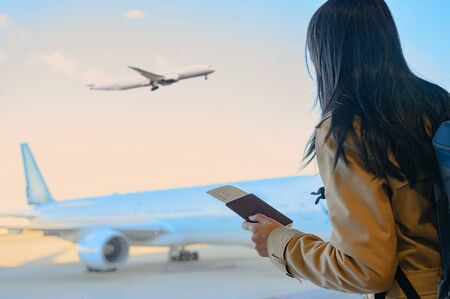 woman passenger holding in hand passport and boarding pass standing by for boarding in terminal gate, aircraft docking in terminal waiting for services under schedule time or delay in additional maintenance services required