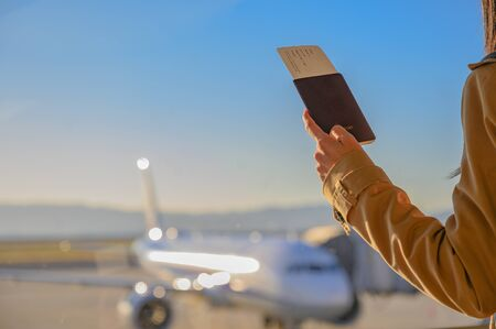 passport and boarding pass in hand of passenger woman stand by for boarding in counter gate, aircraft docking in terminal wait for service under schedule time or delay in additional maintenance service required