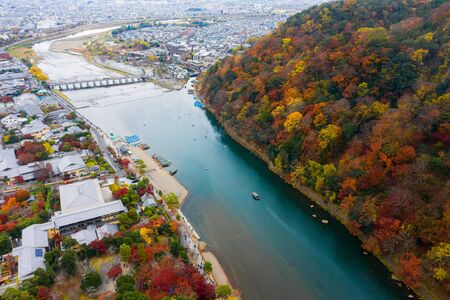Top aerial view of the mountain river with the town city in scenery view of autumn, Arashiyama in Kyoto city of Japan in autumn season change on mountain along the river, popular and famous place for tourist visit Japan