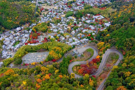 top aerial of scenery autumn view of Japan countryside, curve of road building along up to the hills mountain and town city in background  Фото со стока