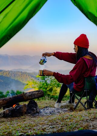 woman traveller with hot drink in front of living tent, prepare hot drink in the morning, wild and adventure trip of alone woman Stok Fotoğraf
