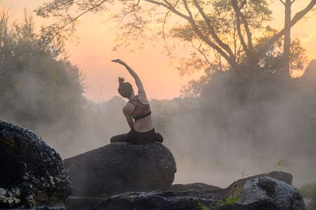 young woman in action of yoga practice in steaming hot spring water, the nature yoga exercise in hot spring steaming water at morning sunrise