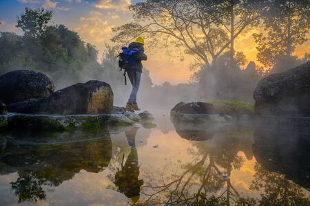 woman trekking alone on the lake of forest mountain with hot spring water flowing the lake in the morning,