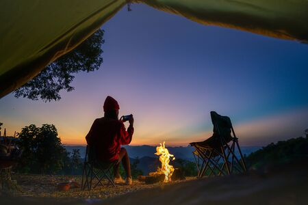 view from tent of woman traveller camping in campfire enjoy taking photo at the sunset Stok Fotoğraf