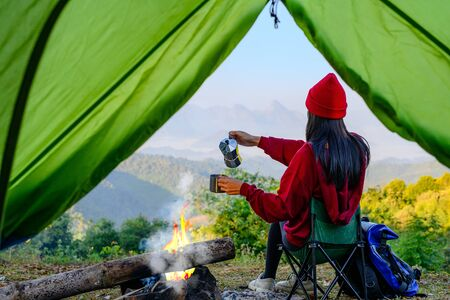 view of tent of woman traveller enjoy hot drink in front of living tent, prepare hot drink in the morning, wild and adventure trip of alone woman