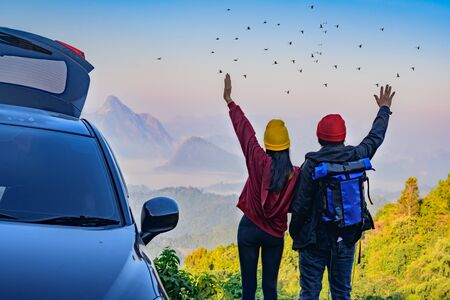 Couple lover standing beside car travel with enjoy the nature of mist in the mountain at sunrise morning, opening arm cheerfully life to the flock of bird Stok Fotoğraf
