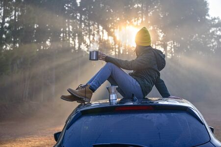 Woman traveller enjoy coffee time on her owns roof of the car with scenery view of the sunrise lightbeam in the forest Stok Fotoğraf