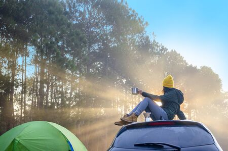 Woman traveller enjoy coffee time on her owns roof of the car with scenery view of the forest and light of mist morning in background Stok Fotoğraf