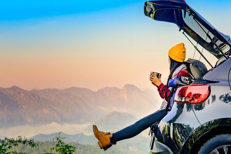 Woman traveller enjoy coffee time on back storage of car with scenery view of the mountain and mist morning in background