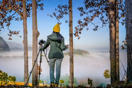 woma traveller or photographer in motion of enjoy the nature moning of the mist and foggy flowing in between the hills mountain