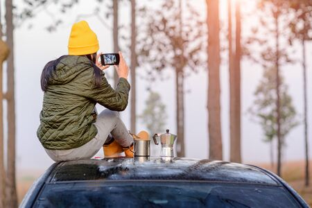 Woman traveller enjoy coffee time and taking photo on her owns roof of the car with scenery view of the mountain and mist morning in background Stok Fotoğraf