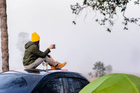 Woman traveller enjoy coffee time on her owns roof of the car with scenery view of the mountain and mist morning in background