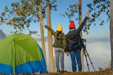 couple lover camper are enjoy the nature life of travel on the peak of mountain with full around of the nature mist on the hills, cheerfully life of the nature surrounding Stok Fotoğraf