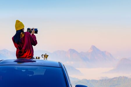 Woman traveller photographer sitting to takes a photo shot on her owns roof of the car with scenery view of the mountain and mist morning in background Stok Fotoğraf