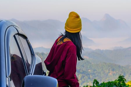 young woman standing beside of the car roof with enjoy the nature of mist in the mountain at sunrise morning.