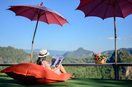 young woman sitting on pillow sofa outdoor on balcony terrace of the cefe, enjoy mountain view with offline social media by reading a book comfortable Stok Fotoğraf